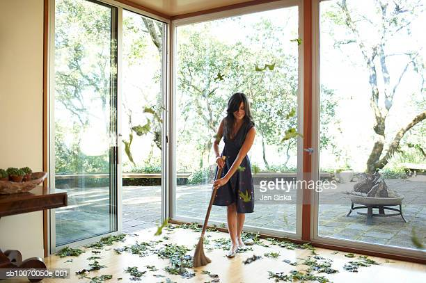 Woman cleaning up fallen leaves on floor, smiling