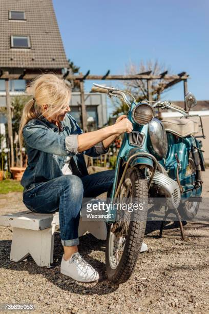 Woman cleaning vintage motorcycle