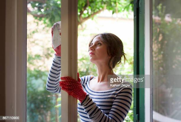 Woman cleaning window, view from inside