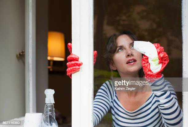 Woman cleaning window, view from outside