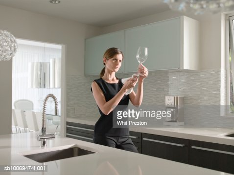 Woman cleaning wine glass in kitchen : Foto de stock