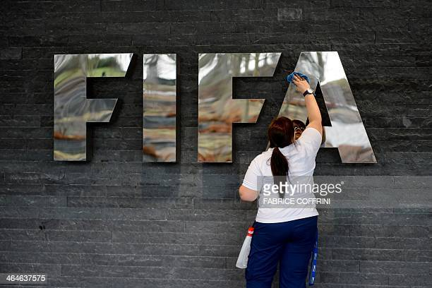 A woman cleans a FIFA sign prior to the arrival of Brazilian President Dilma Rousseff on January 23 2013 at the football's world governing body's...