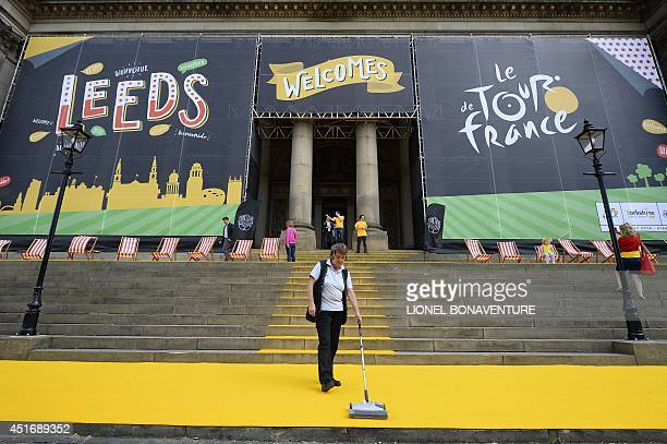 A woman cleans a yellow carpet on July 4 2014 in front of the city hall of Leeds northern England before a family picture with French Republican...