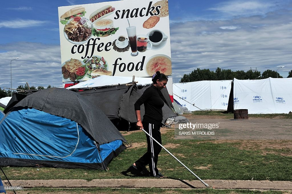 A woman cleans an area at a makeshift camp set near a gas station some 20 km from the Greek-Macedonian border, on 25 May, 2016 in Polykastro. In an operation which began shortly after sunrise on May 24, hundreds of Greek police began evacuating the sprawling camp which is currently home to 8,400 refugees and migrants, among them many families with children, an AFP correspondent said. At its height, there were more than 12,000 people crammed into the site, many of them fleeing war, persecution and poverty in the Middle East and Asia, with the camp exploding in size since Balkan states began closing their borders in mid February in a bid to stem the human tide seeking passage to northern Europe. / AFP / SAKIS