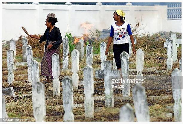 A woman cleans graves at Heros Cemetery in Dili East Timor where Indonesian soldiers and police who were killed during Indonesia's occupation of East...