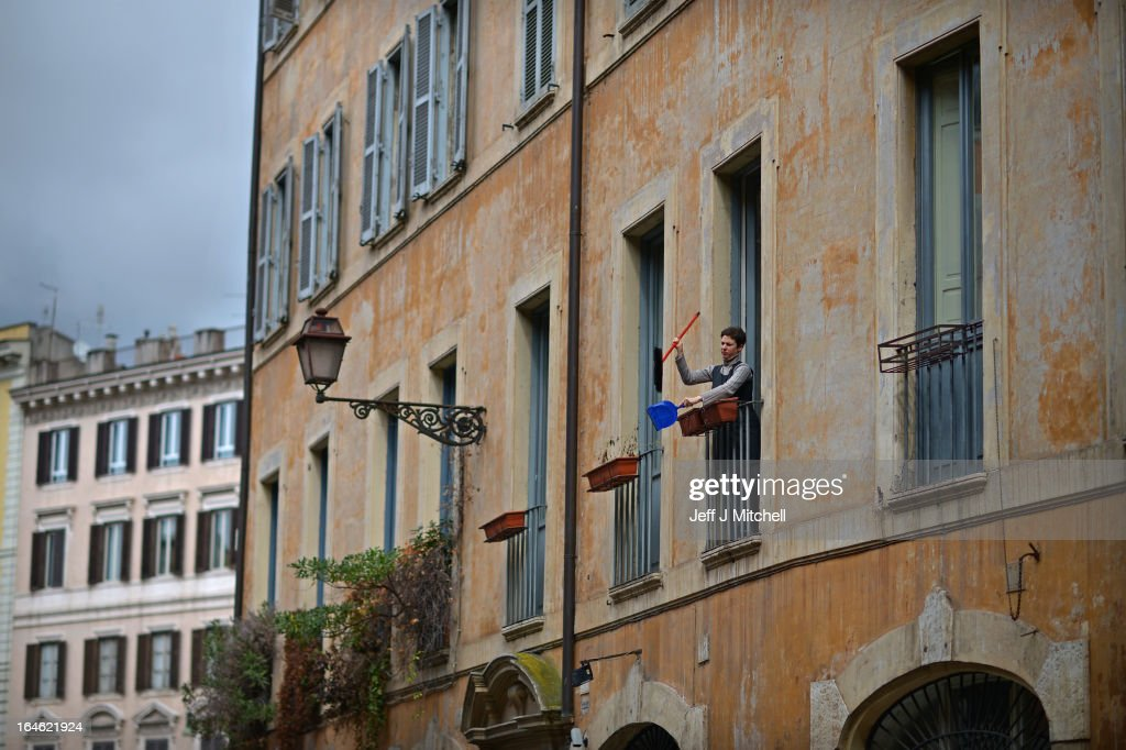 A woman cleans her dust bucket from a window in Piazza Navona on March 25, 2013 in Rome, Italy. Pope Francis yesterday led his first mass of Holy Week as pontiff by celebrating Palm Sunday in front of thousands of faithful and clergy.