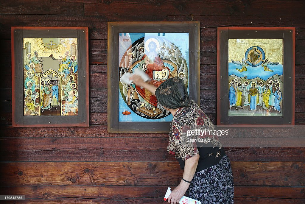 A woman cleans icons that adorn the exterior of the wooden church at Titan park on September 7, 2013 in Bucharest, Romania. The church, called the Biserica Pogorarea Sfantului Duh, was built in the 1990s. While Romania's economic output has risen significantly since it joined the European Union in 2007, it still lags in infrastructure development and the fight against corruption.