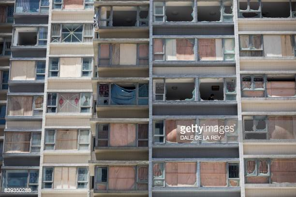 TOPSHOT A woman cleans inside her apartment in a damaged residential building in the aftermath of Typhoon Hato in Macau on August 26 2017 The Chinese...