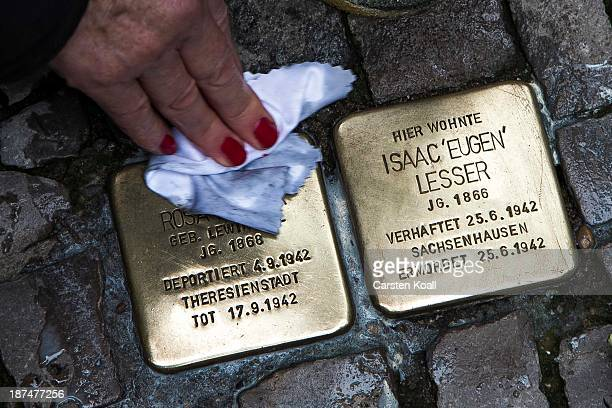 A woman cleans so called Stolpersteine brass stumbling blocks to commemorate the 75th anniversary of the Kristallnacht pogroms on November 9 2013 in...