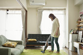 A woman cleans the room with a vacuum cleaner