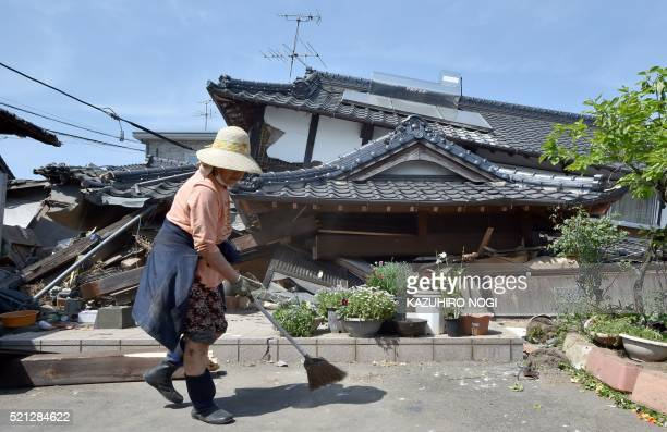TOPSHOT CORRECTION A woman cleans up in front of her collapsed house in the town of Mashiki Kumamoto prefecture on April 15 2016 A strong 65magnitude...