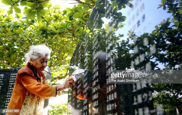 A woman cleans with a cloth the names of her mother and other relatives engraved on the Cornerstone of Peace at the Peace Memorial Park on the 72nd...