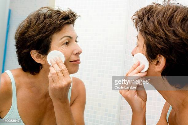 Woman cleansing face with cotton wool pad