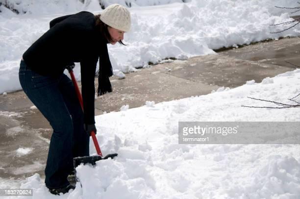 Frau ausführen Schnee von der Auffahrt