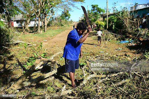A woman clears a fallen tree outside her home in Vanuatu's capital Port Vila on March 17 2015 after Cyclone Pam ripped through the island nation The...