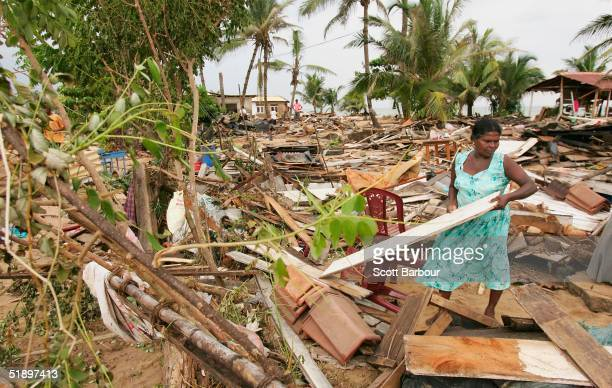 A woman clears away debris from where her home once stood after the massive tsunami wave swept across coastal Sri Lanka December 28 2004 in Colombo...