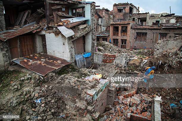 A woman clears debris from her collapsed home on July 29 2015 in Bhaktapur Nepal Three months after the earthquake that hit Nepal on April 25th and...