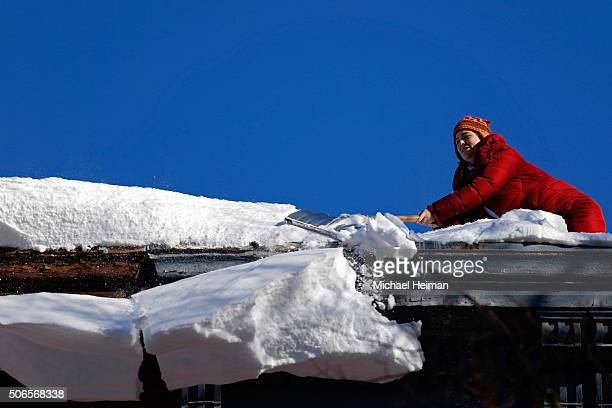 A woman clears snow off of her roof on January 24 2016 in the Brooklyn borough of New York City Most of New York's streets were cleaned up overnight...