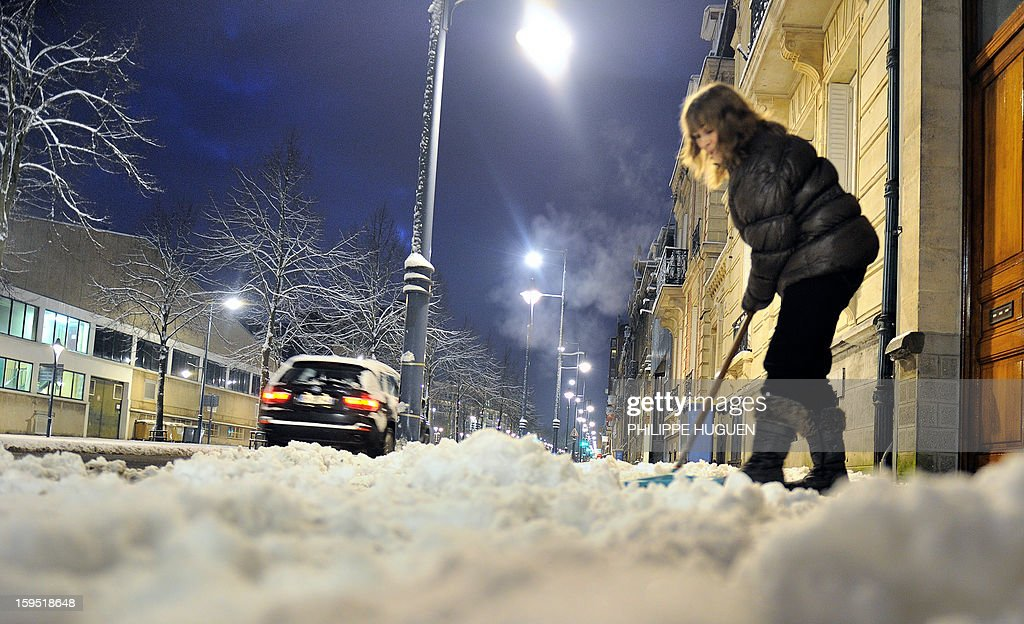 A woman clears up fresh snow from the sidewalk in front of her home on january 15, 2013 in Arras, northern France, after snow blanketed several French departments. Road traffic is affected by snowfalls in northern and eastern regions.