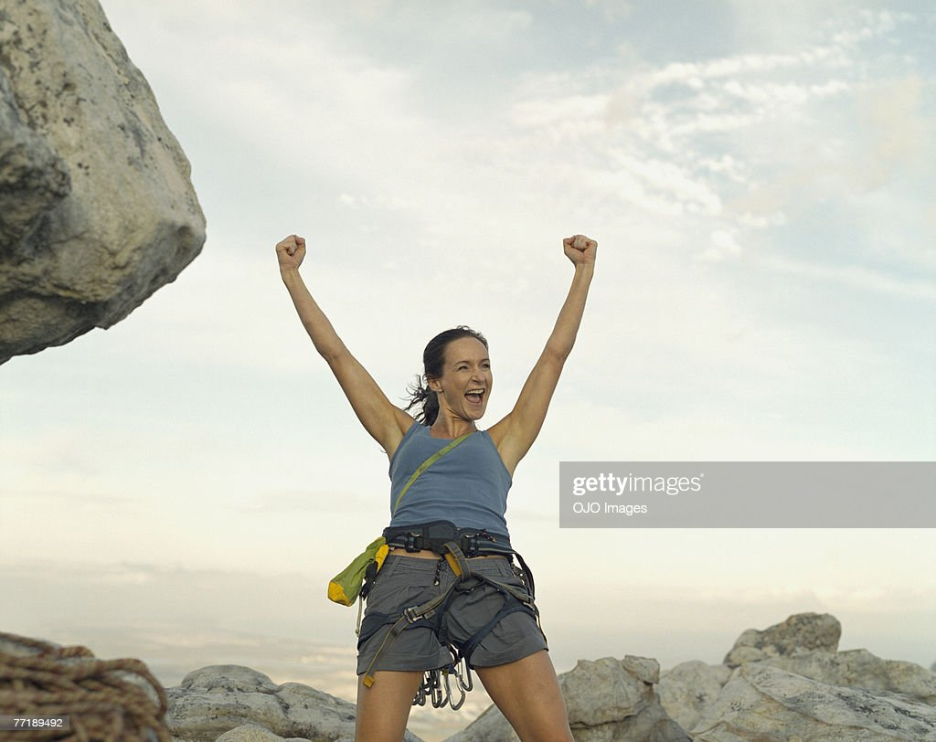 A woman climber at the top of a mountain victorious : Stock Photo