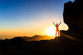 Woman successful hiking climbing silhouette in mountains, motivation and inspiration in beautiful sunset and ocean. Female hiker with arms up outstretched on mountain top looking at beautiful night su