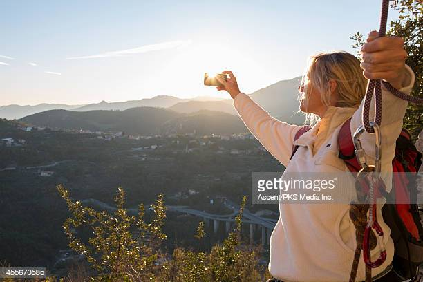 Woman climber takes picture with smart phone, sun