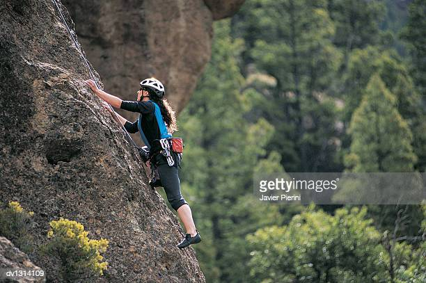 Woman Climbing a Rock Face