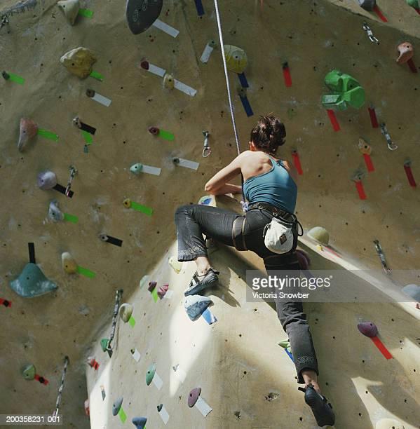 Woman climbing gym wall