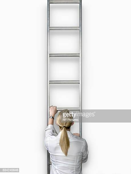 Woman climbing ladder, back view