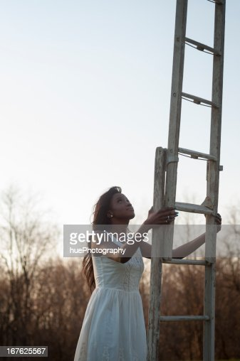 Woman Climbing Ladder : Stock Photo