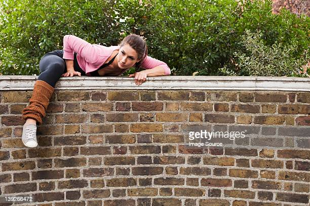 Woman climbing over over wall