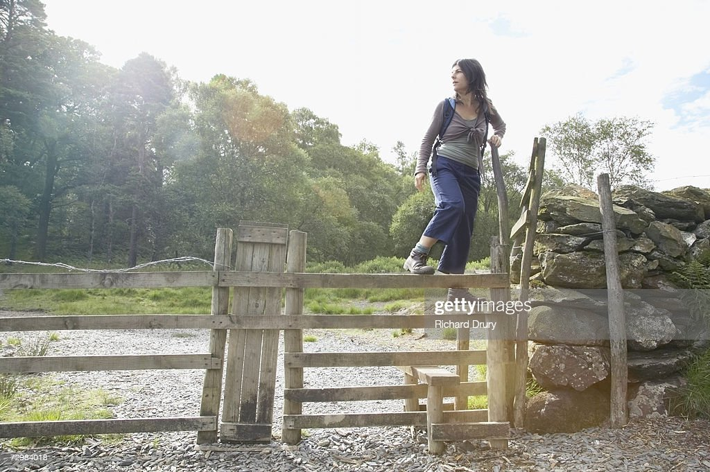Woman climbing over stile : Stock Photo
