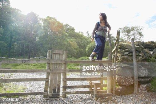 Woman climbing over stile : Stock Photo