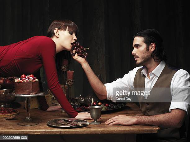 Woman climbing over table, man feeding her grapes