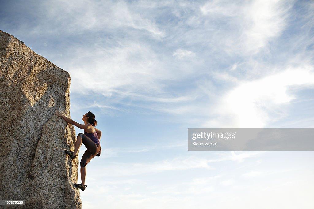 Woman climbing rock side