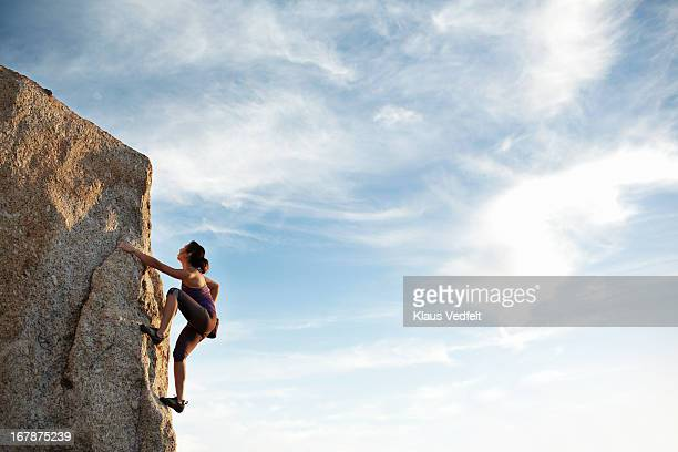 Woman climbing rock side
