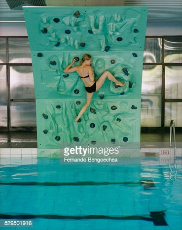 Woman Climbing Rock Wall Hanging Over Swimming Pool Stock Photo Getty Images