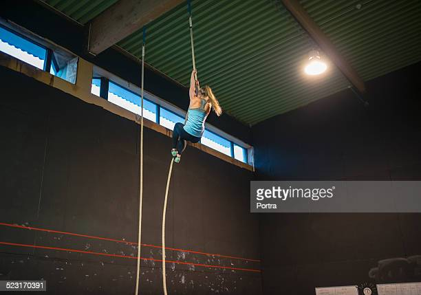 Woman climbing rope in gym