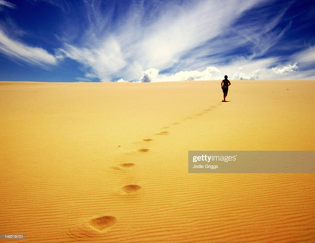 Woman climbing sand dunes : Stock Photo