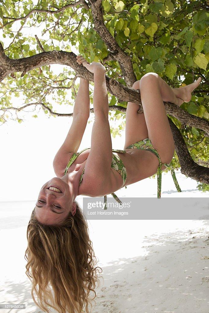 Woman climbing tree on tropical beach : Stock Photo
