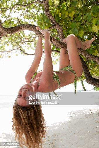 Woman クライミングの木がトロピカルなビーチ : ストックフォト