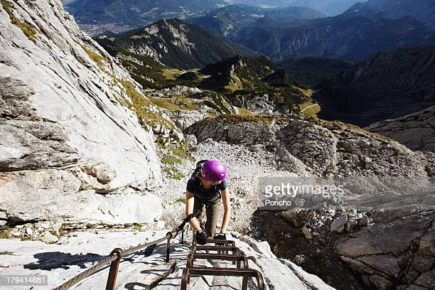 woman climbing up a ladder of a via ferrata