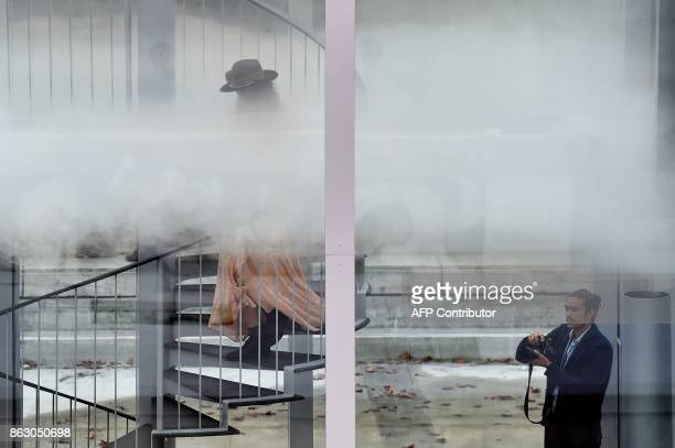 A woman climbs down a staircase in a glass cube containing an olfactory cloud Le Nuage Parfumé or OSNI 1 launched by Cartier and displayed outside...