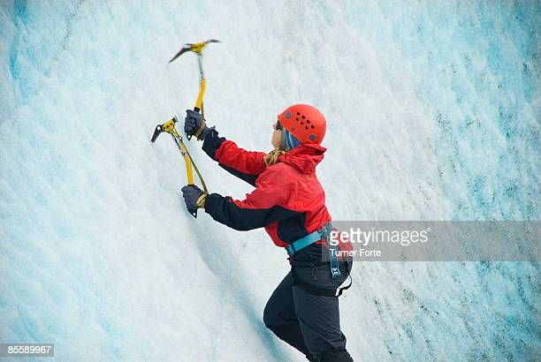 Woman climbs ice wall on glacier