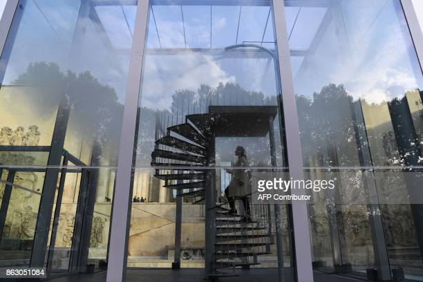 A woman climbs on a staircase in a glass cube containing an olfactory cloud Le Nuage Parfumé or OSNI 1 launched by Cartier and displayed outside the...
