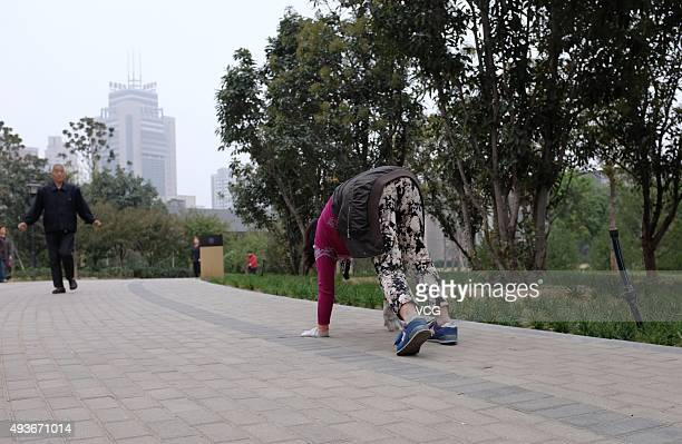 A woman climbs on hands and feet for exercise at Zhengzhou Shang City Archaeological Site Park on October 22 2015 in Zhengzhou Henan Province of...