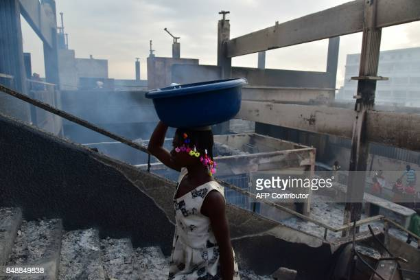 TOPSHOT A woman climbs stairs in the market after a fire devastated the building during the night on September 18 2017 in Abobo neighborhood of...