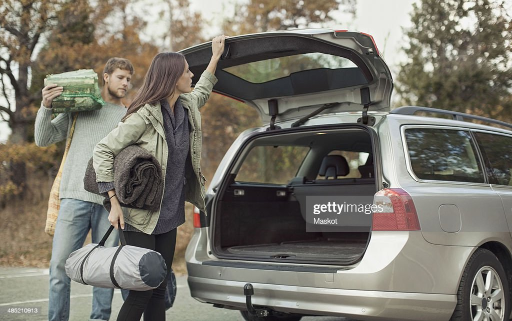 Woman closing car boot while camping with man