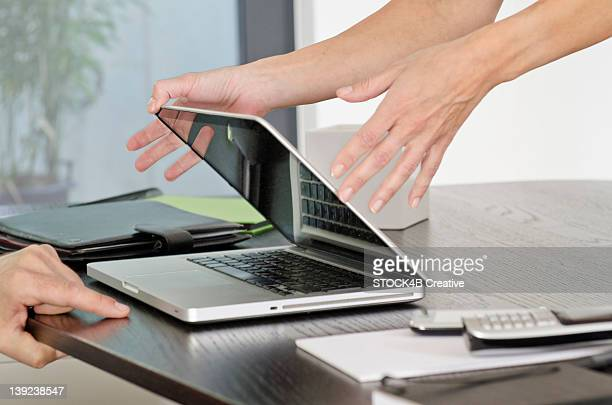 Woman closing laptop at desk