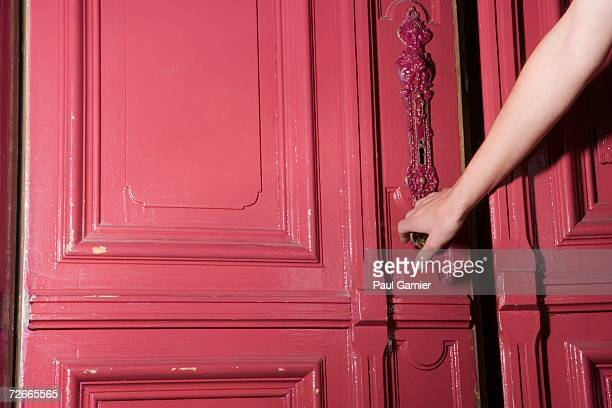 Woman closing pink door of apartment
